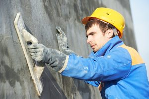 Young builder worker at facade plastering work during industrial