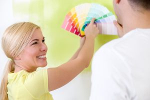 Happy couple choosing colors for painting house, concept of deco